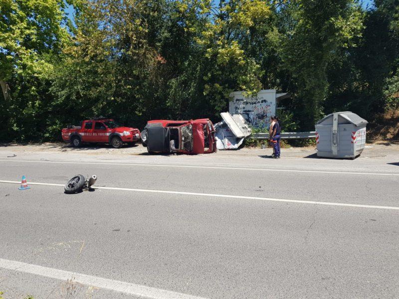 Schianto tra moto e un'auto che si ribalta e si abbatte sui cassonetti – FOTO E VIDEO